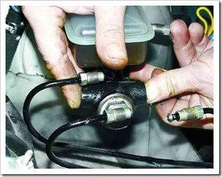 Закрываем пальцами отверстия под тормозные трубки